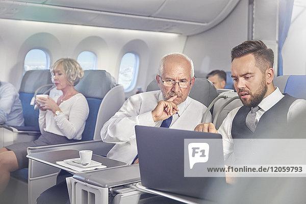 Geschäftsleute bei der Arbeit am Laptop in der ersten Klasse im Flugzeug