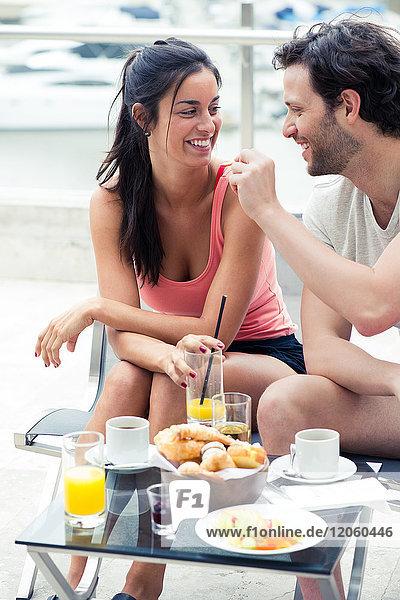 Freund füttert Freundin Frühstück im Freien
