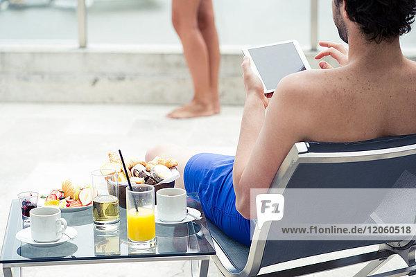 Der Mann entspannt sich am Pool mit einem digitalen Tablett