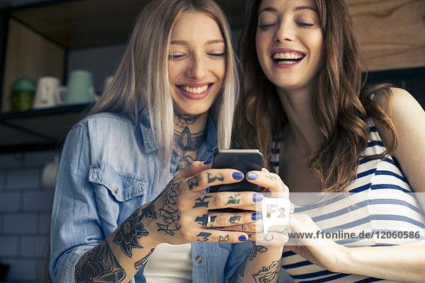 Frauen  die Smartphones anschauen und gemeinsam lachen