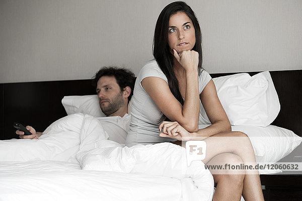 Frau sitzt im Bett  während ihr Mann fernsieht.