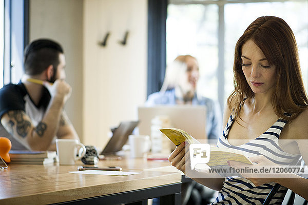 Frau liest Buch im gemeinsamen Büro