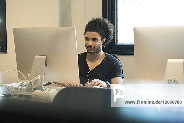 Junger Mann mit Desktop-Computer