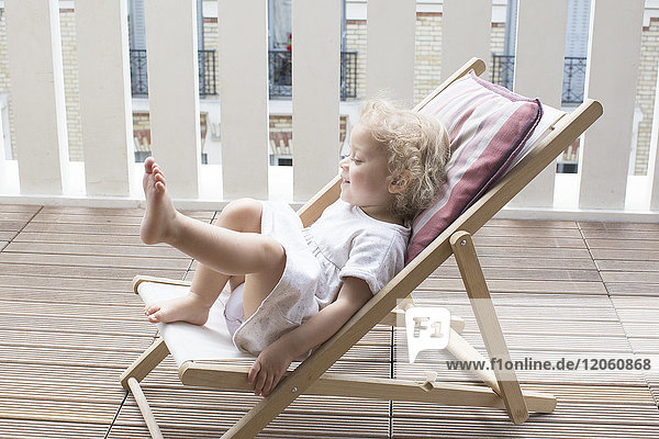 Little girl sitting on deckchair