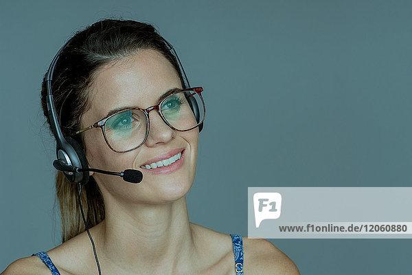 Junge Frau mit Kopfhörer  fröhlich lächelnd