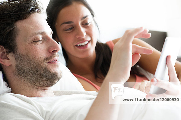 Paar mit digitalem Tablett im Bett