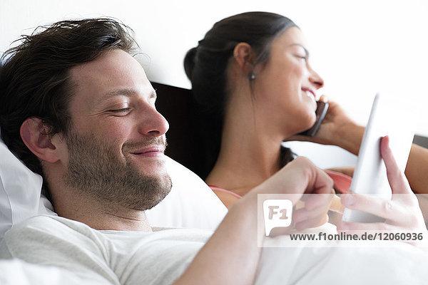 Paar entspannt im Bett  Mann mit digitalem Tablett  während Frau telefoniert