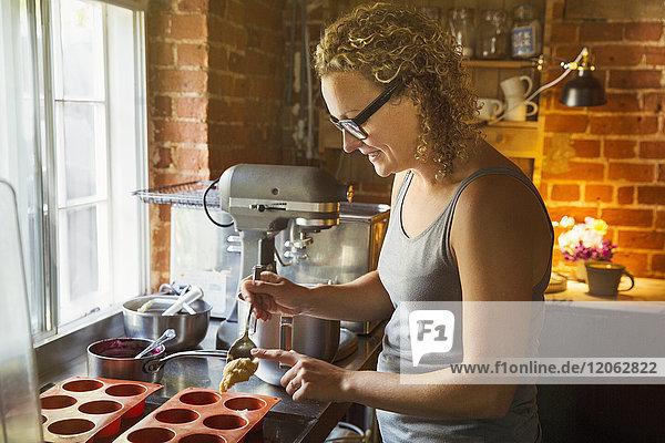 Seitenansicht einer Frau  die in einer Küche steht  backt und Silikonformen füllt.
