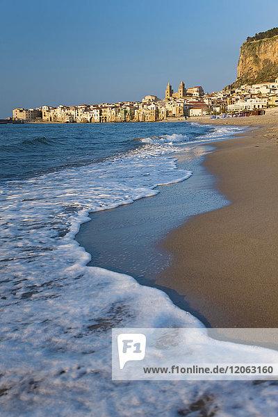 Blick entlang der Küstenlinie mit Sandstrand  in der Ferne die Stadt.