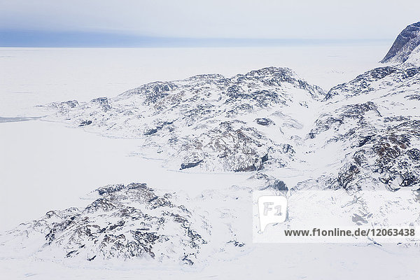 High angle view of rocky winter landscape covered in snow and ice  with ocean in the distance.