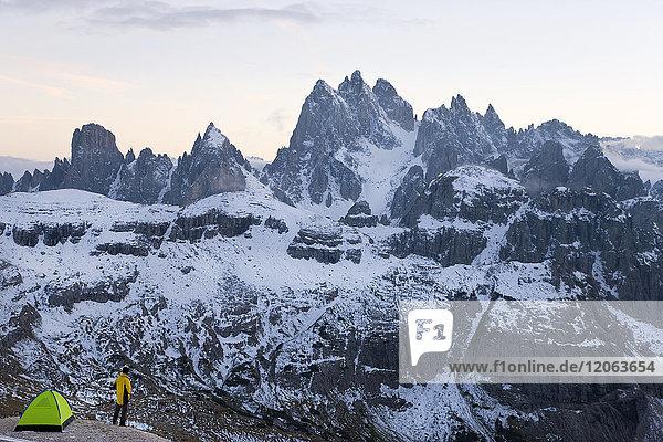 Mann steht neben dem Zelt  das inmitten einer schneebedeckten Bergkette aufgestellt ist.