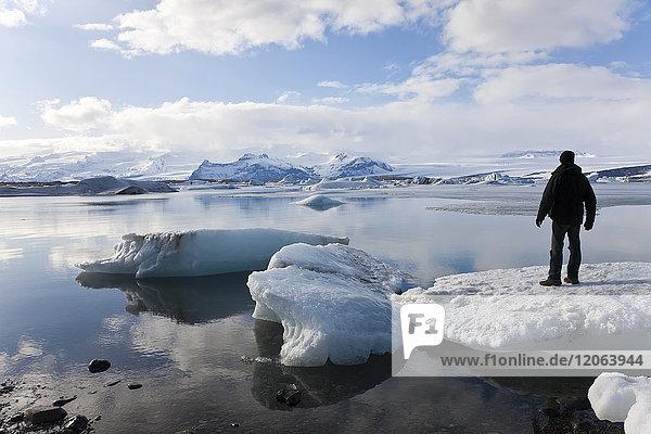Rückansicht einer auf dem Eisschild stehenden Person auf einer Gletscherlagune mit Eisbergen  in der Ferne Berge.