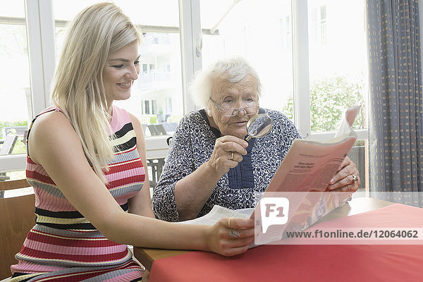 Woman reading newspaper with her mother at rest home