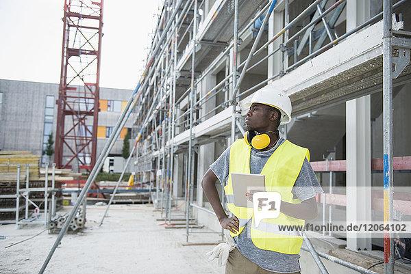 Construction worker holding digital tablet at building site