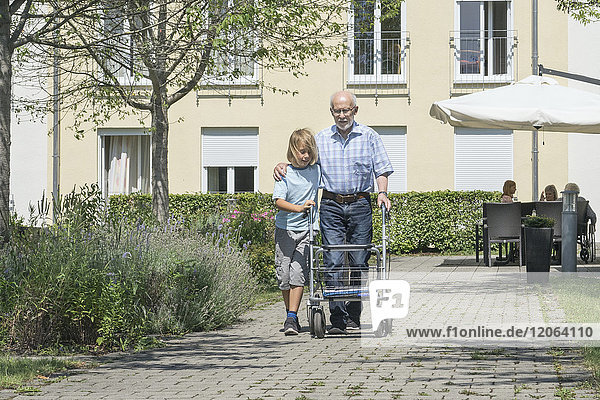 Boy helping grandfather with mobility walker at rest home park