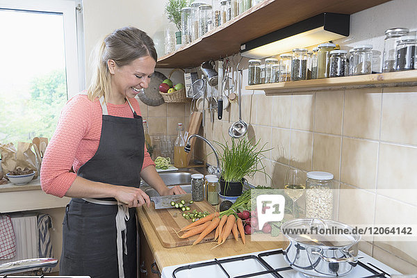 Young woman cutting asparagus in kitchen