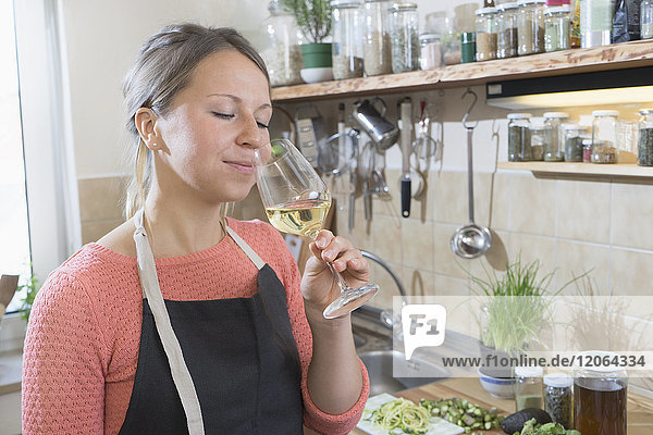 Young women smelling white wine in kitchen