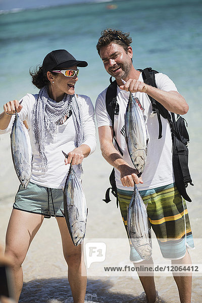 Man and woman with fresh fish at the beach