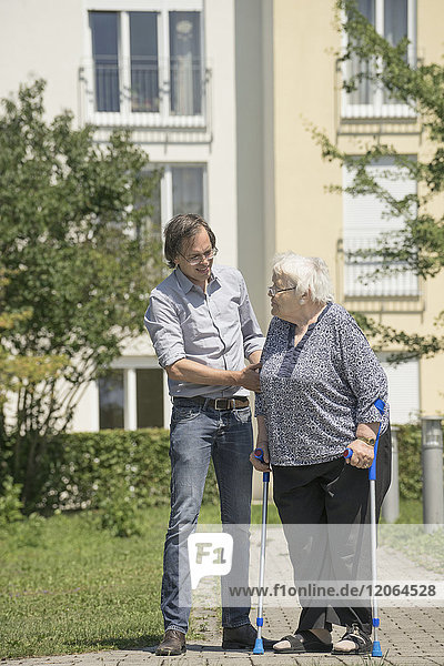 Son walking with disabled mother on crutches