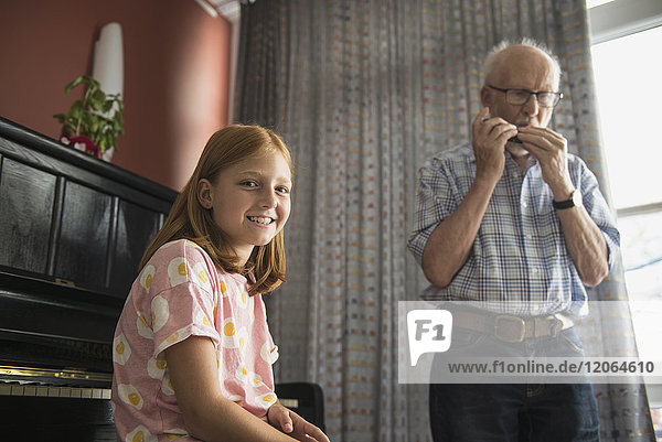Granddaughter listening while grandfather blowing harmonica instrument