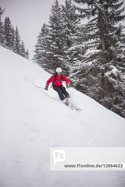 Man skiing downhill on snow