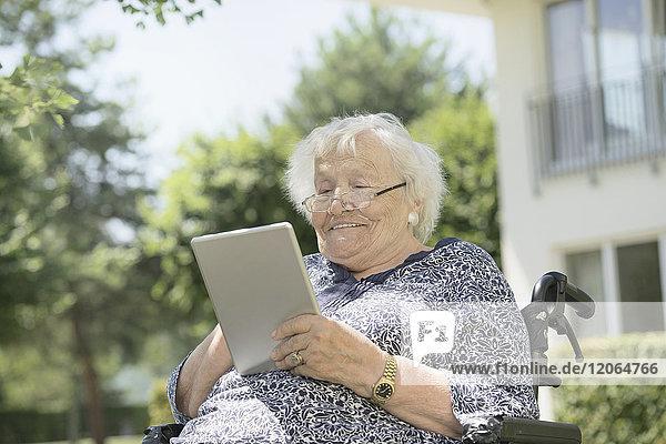 Senior woman using digital tablet on wheelchair