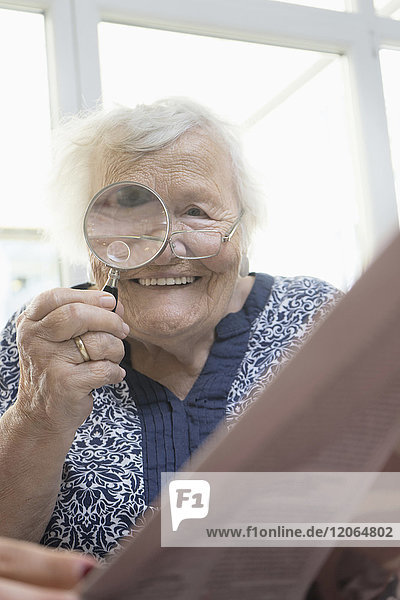 Senior woman reading newspaper with magnifier glass