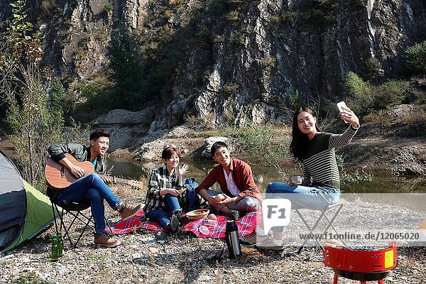 Young men and women picnic in the mountains