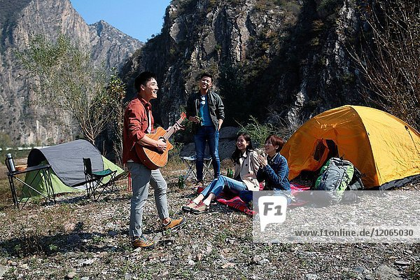 Young men and women camping in the mountains
