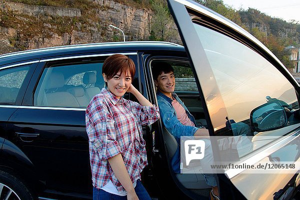 Young men and women travel by car