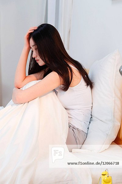 The depressed young woman sat on the bed in the bedroom