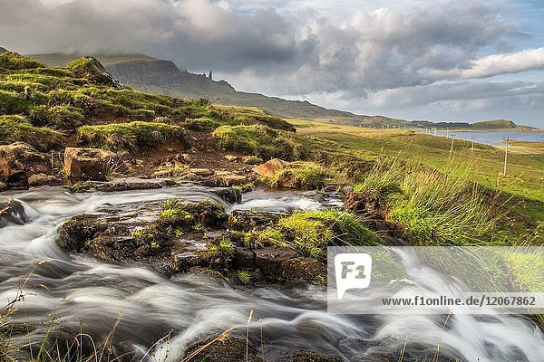 Bride's veil waterfall with Old man of Storr in the background. Isle of Skye  Scotland.