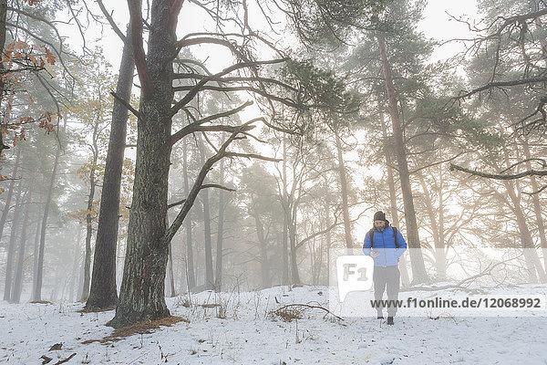 Ein Mann  der durch einen verschneiten Wald geht.