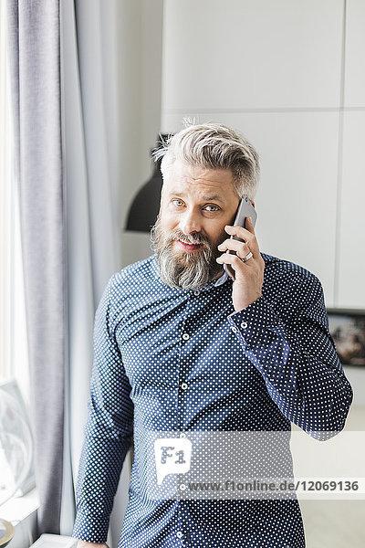 Ein Mann in einem gefleckten Hemd  der auf einem Handy spricht.