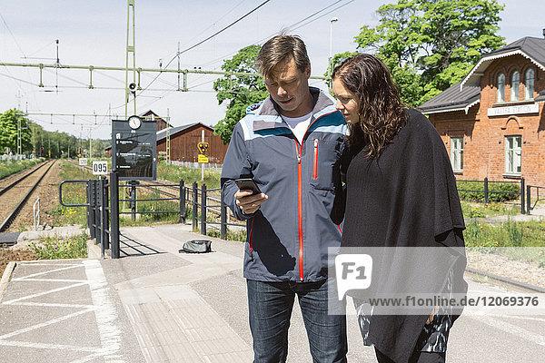 Pärchen beim Blick auf das Smartphone auf dem Bahnsteig