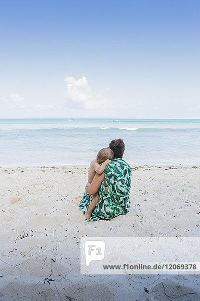 Mutter und Sohn sitzen am Strand in Kenia