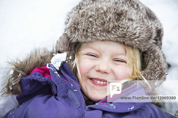 A happy young girl playing in the snow