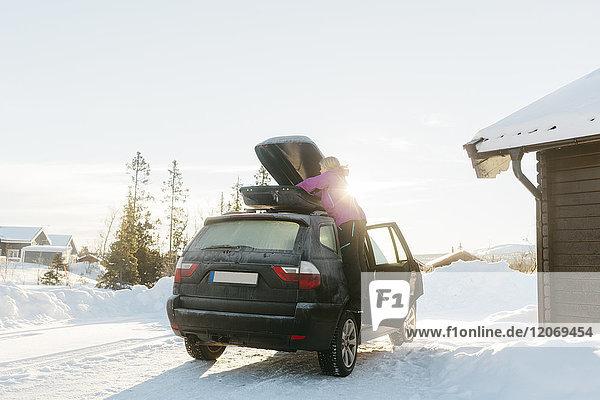 Frau beim Auspacken eines Autos im Winter