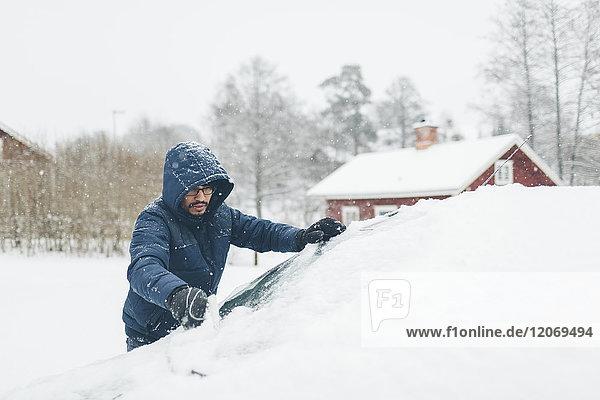 Der Mann räumt den Schnee aus seinem Auto.