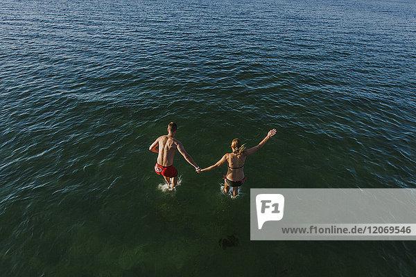Ein Mann und eine Frau  die ins Meer springen.