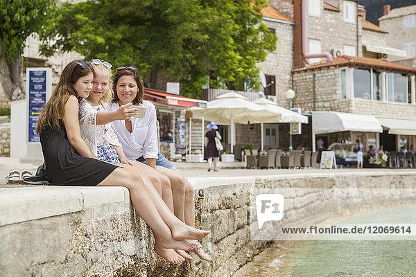 Eine Mutter und zwei Töchter sitzen auf einer Mauer über dem Meer.