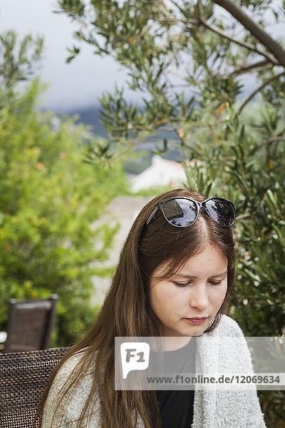 Eine junge Frau sitzt draußen.