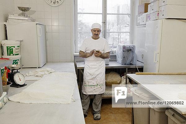 Koch mit Smartphone in der Küche