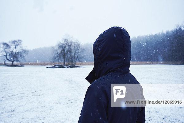 Ein Mann in einer schwarzen Jacke steht in einem schneebedeckten Feld.
