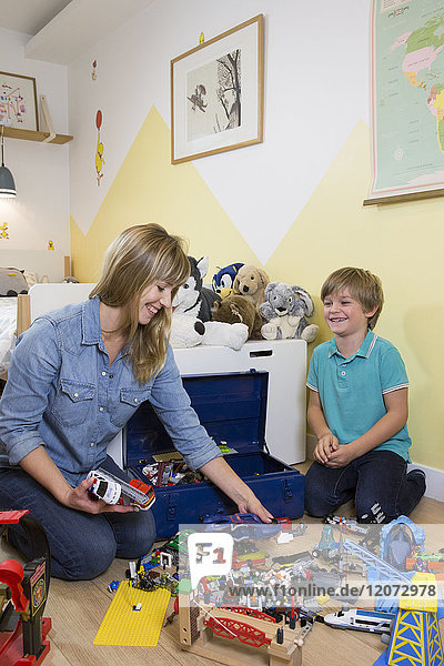 A child playing in his room with his mother.