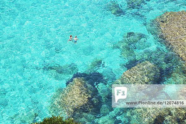 People swimming in the emerald waters of Cala Mitjana  Menorca  Balearic Islands  Spain  Mediterranean  Europe