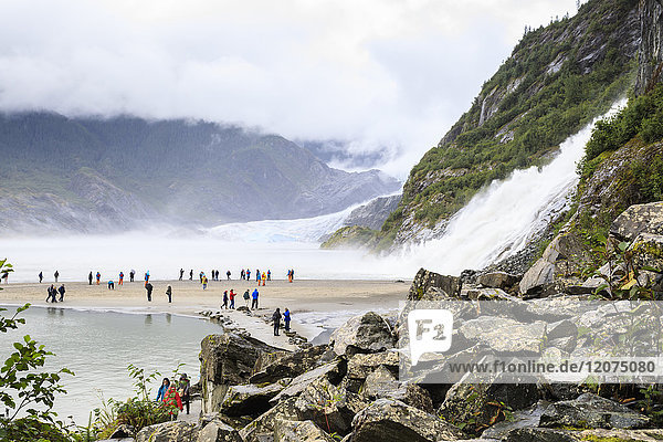 Mendenhall Glacier and Lake  Nugget Falls Cascade  mist  visitors on a beach  Nugget Falls Trail  Juneau  Alaska  United States of America  North America