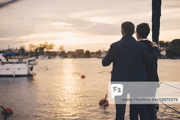 Rear view of senior couple standing on bow of yacht during sunset
