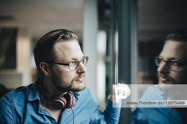 Thoughtful mid adult businessman looking through window at office