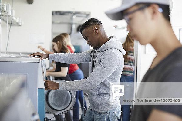Studentinnen und Studenten in der Waschmaschine im Waschsalon
